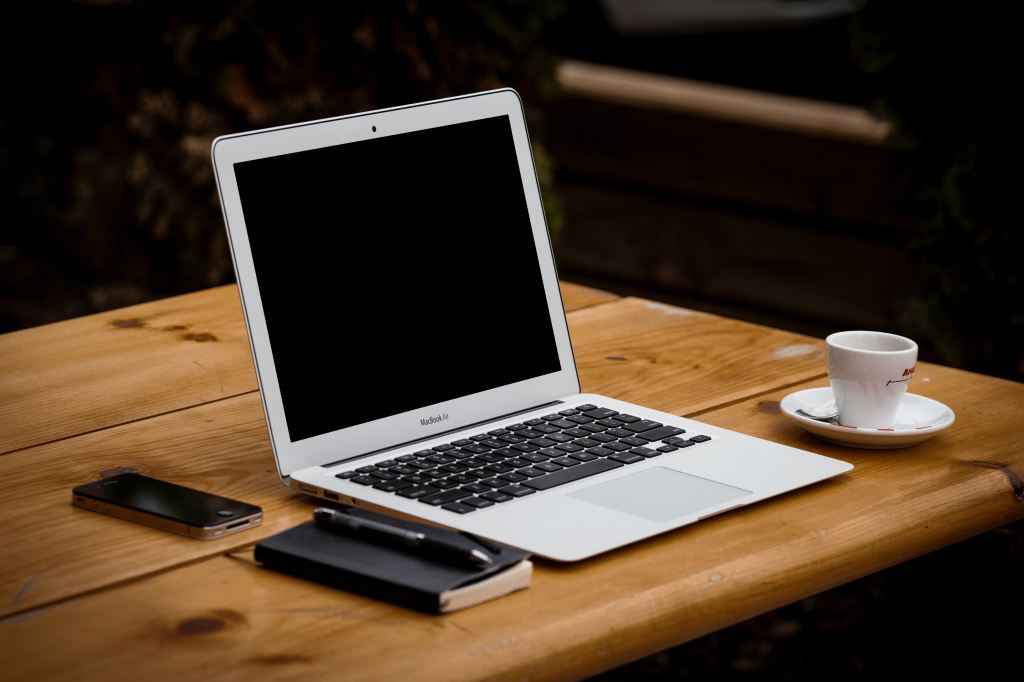 An image of a Macbook air on a wood table with a phone and notebook in parallel and a coffee cup to one side.