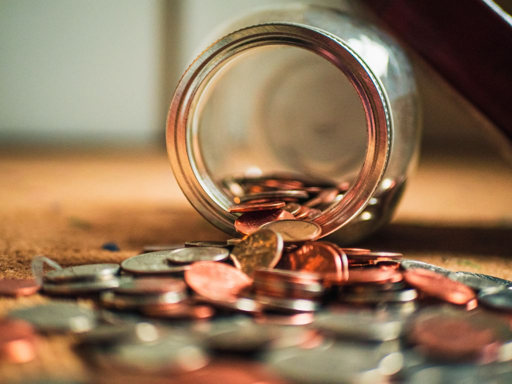 A jar of coins spilled on a floor. More coins are on the floor than still in the jar.