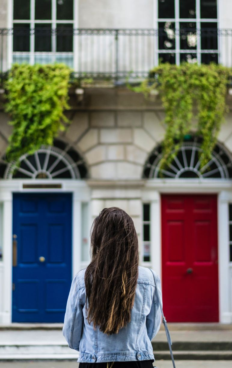 A woman stands in front of two doors, one blue, one red